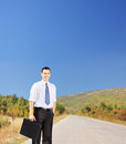 Young smiling businessperson holding a suitcase on a road leather an open shot with tilt and shift lens Royalty Free Stock Photo