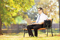 Young smiling businessperson sitting on bench and working on a l wooden laptop in park Royalty Free Stock Image