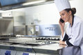 Young smiling chef standing next to work surface phoning in professional kitchen Stock Photos