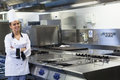 Young smiling chef standing next to work surface in professional kitchen Royalty Free Stock Photography