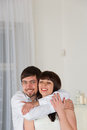 Young smiling couple embrace each other standing at home in living room with area for copy space Stock Images