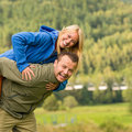 Young smiling couple having fun piggyback riding nature Royalty Free Stock Images
