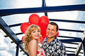 Young smiling couple with red balloons happy on the bridge Stock Photography