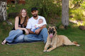 Young Smiling Family and their Dog in the Park Royalty Free Stock Photo