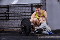 Young smiling father and little cute son with dumbbells against brick wall at the cross fit gym. Royalty Free Stock Photo