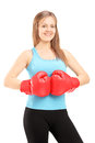 Young smiling female athlete wearing red boxing gloves and posing isolated on white background Royalty Free Stock Photo