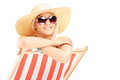 Young smiling female with a hat posing on a beach chair isolated white background Stock Photo