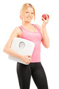 Young smiling female holding a weight scale and a red apple isolated on white background Stock Images