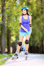 Young smiling female on rollers skating in a park full length portrait Royalty Free Stock Photography