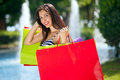 Young smiling female shopping carrying colourful bags in the background fountains along a mall Stock Image