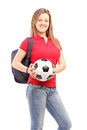 Young smiling female student holding a soccer ball isolated against white background Stock Image
