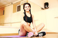 Young smiling fit woman sitting on yoga mat at gym Royalty Free Stock Photo