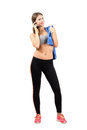 Young smiling fitness woman talking on the mobile phone full body length portrait isolated over white background Royalty Free Stock Photos