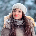 Young smiling girl in a hat outdoors in winter forest Royalty Free Stock Photo