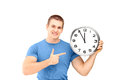 Young smiling guy standing and pointing on a wall clock Royalty Free Stock Images