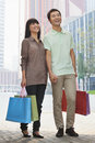 Young smiling happy couple walking outdoors in beijing with colorful shopping bags in hands Stock Photos
