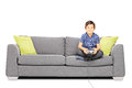 Young smiling kid seated on a sofa playing video games isolated white background Royalty Free Stock Photos