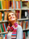 Young smiling lady looking upwards in library Stock Photography
