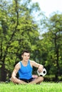 Young smiling male athlete sitting down on a grass with ball in green soccer park Stock Image