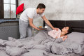 Young smiling man bring breakfast for his wife in bed and wake h Royalty Free Stock Photo