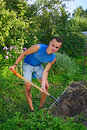 Young smiling man digging a garden bed for planting Apple trees Royalty Free Stock Photo