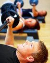 Young smiling man lifting weights at the gym Stock Photography