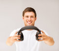 Young smiling man offering headphones picture of Royalty Free Stock Photography