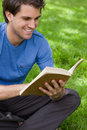 Young smiling man reading a book while siting on the grass Stock Image
