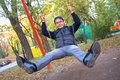 Young smiling man on swing Royalty Free Stock Photos