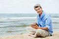 Young smiling man with tablet pc on seashore Royalty Free Stock Photography