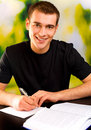Young smiling man writing Royalty Free Stock Photo