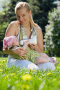 Young smiling mother feeds her baby milk bottle sitting grass spring park Stock Photo