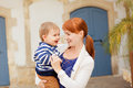 Young smiling mother holding smiling baby boy in the striped jac