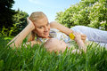 Young smiling mother reclines green grass next to her baby daughter Stock Photo