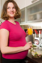 Young smiling pregnant woman in kitchen Royalty Free Stock Images