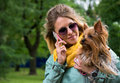 Young smiling pretty blonde woman with yorkshire t talking mobile phone in city park small terrier is on her hands Royalty Free Stock Image