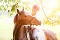 Young smiling rider woman touching lips of horse Royalty Free Stock Photo