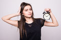 Young smiling woman with alarm clock  white grey wall background. Human face expression. Royalty Free Stock Photo