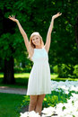 Young smiling woman with arms raised outdoors Royalty Free Stock Photo