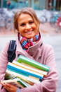 Young smiling woman with backpack holding books Royalty Free Stock Image