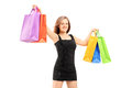 Young smiling woman in black dress holding shopping bags isolated against white background Stock Photography