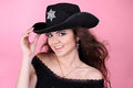 Young smiling woman in black hat on pink Royalty Free Stock Image