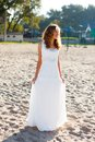 Young smiling woman bride in a white dress on the sunny beach Stock Photos