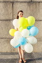 Young smiling woman with bunch of balloons