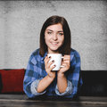 Young smiling woman drinking a cup go coffee square portrait of in blue flannel shirt and black nails from big white mug Stock Photos