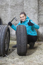 Young smiling woman driver replacing tires showing ok sign girl whilst summer tyres with winter tyres before coming winter Royalty Free Stock Photo