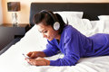 Young smiling woman in headphones listening to the music in bed a blue top and Stock Images