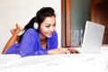 Young smiling woman in headphones using a laptop in bed blue top and Stock Photography