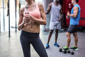 Young smiling woman holding a bottle of water with colleagues behind her in the crossfit gym Stock Image