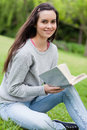 Young smiling woman holding her book while looking at the camera Royalty Free Stock Photos
